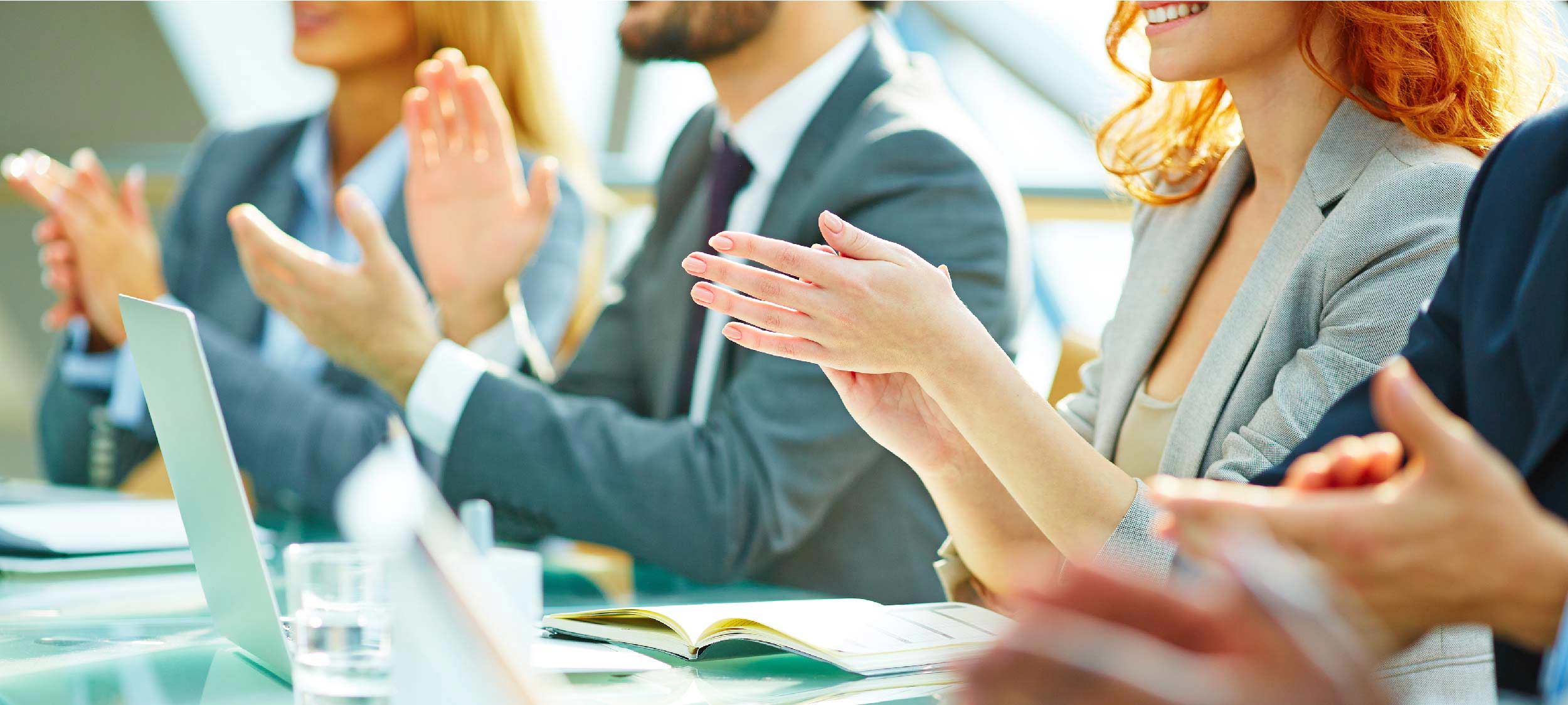 Group of business professionals applauding while sitting