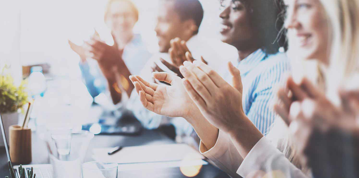 Group of diverse professionals applauding while sitting
